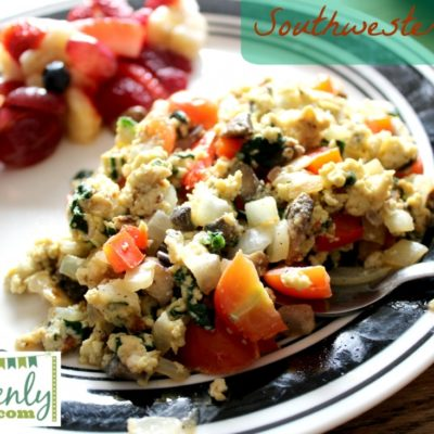Eggs with spinach, tomatoes, and onions with fruit and black and white plate in the back round