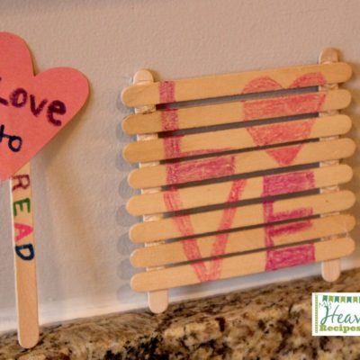 A book mark made of Popsicle sticks and a cut out heart and a Popsicle sign that says Love