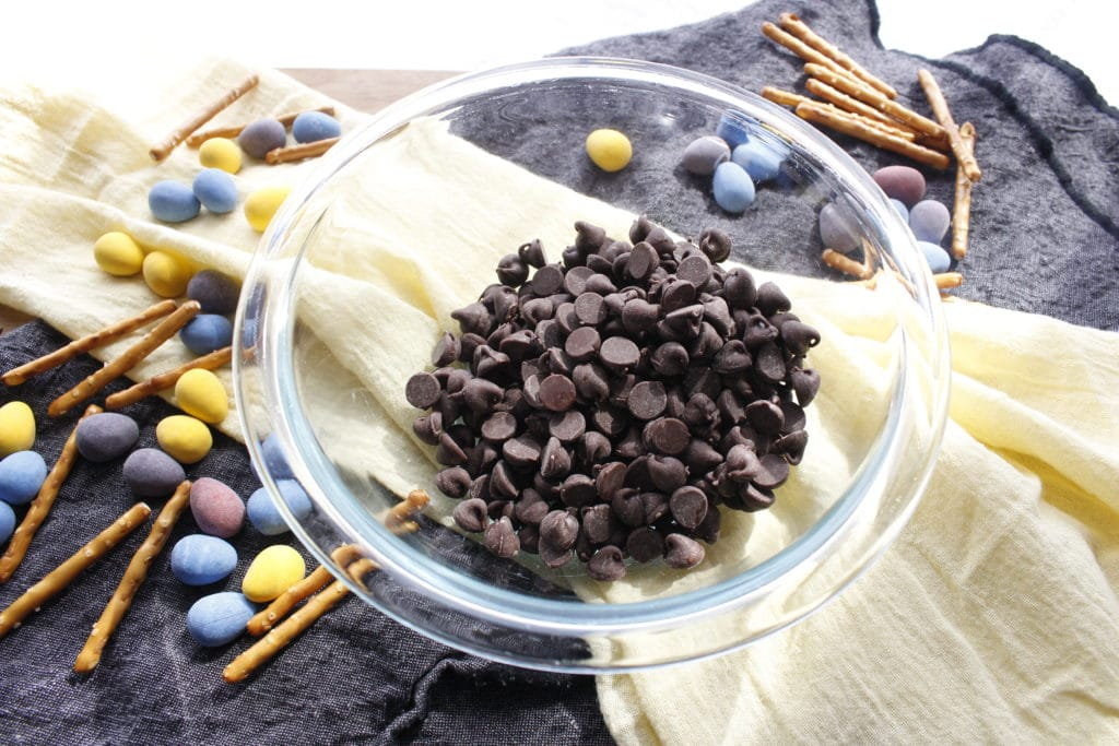 chocolate morsels in a bowl with pretzels on napkins and candy easter eggs