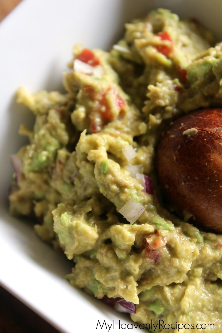 Tight shot of homemade guacamole with avocado pit in a white bowl