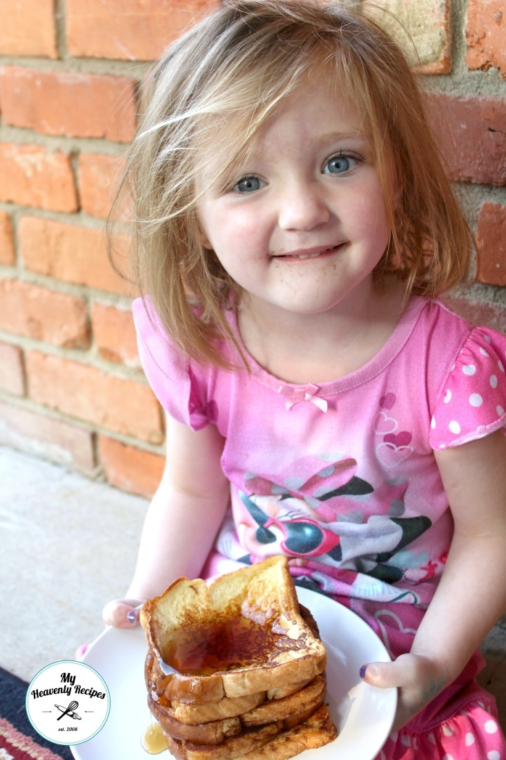 little girl holding a plate of French Toast with syrup