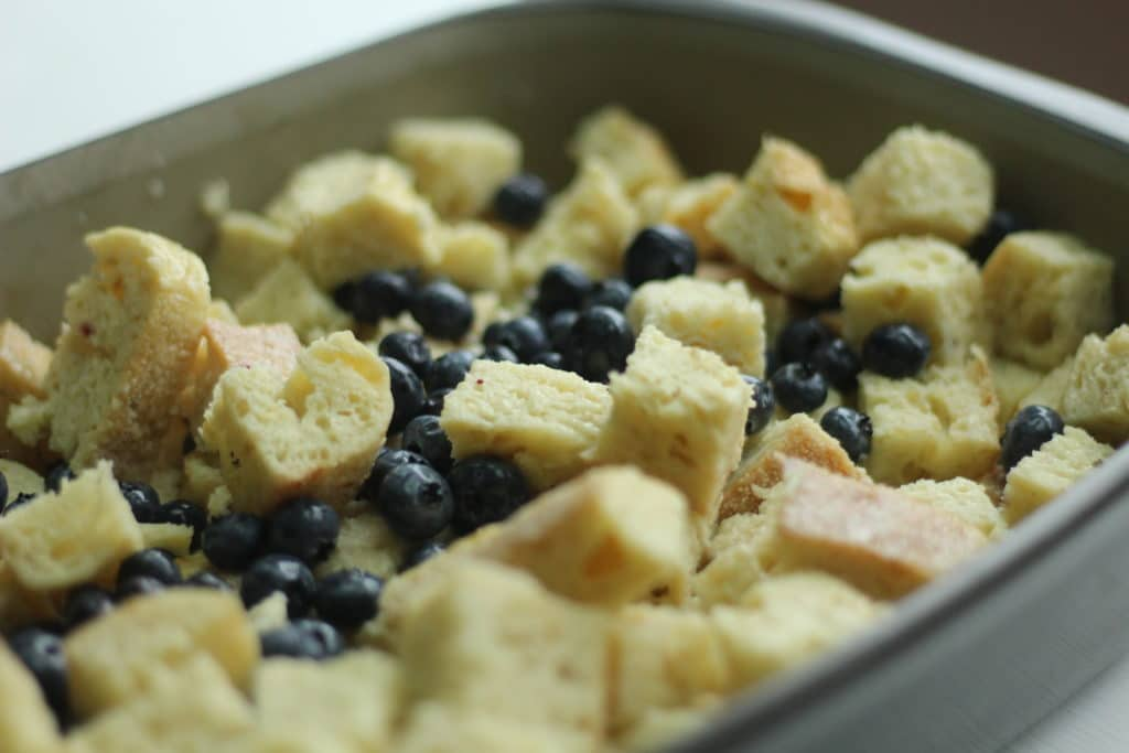 blueberries added to cubed bread in baking dish