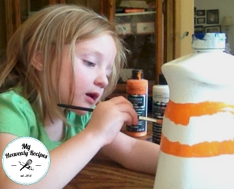 little girl painting a plastic milk jug to look like Halloween candy corn