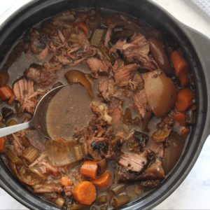 Crock-Pot Pot Roast in slow cooker with spoon and marble background