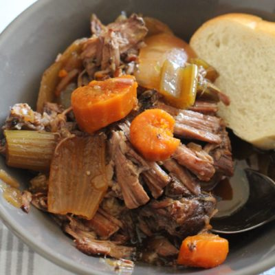 Crock-Pot Pot Roast in gray bowl and piece of bread