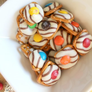 hershey kiss pretzels in a bowl white and m&m's on top of striped hershey kisses and pretzel