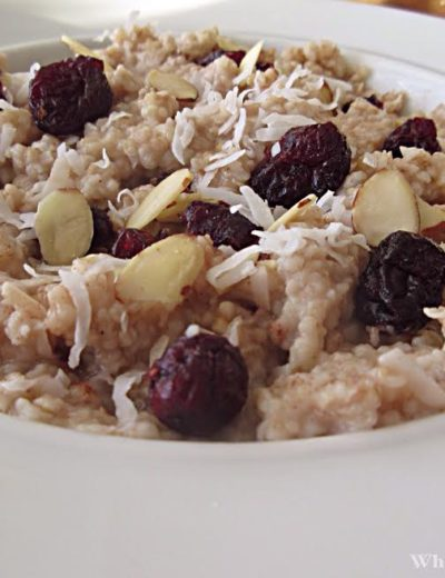 a bowl of steel cut oatmeal topped with coconut, almonds and dried fruit