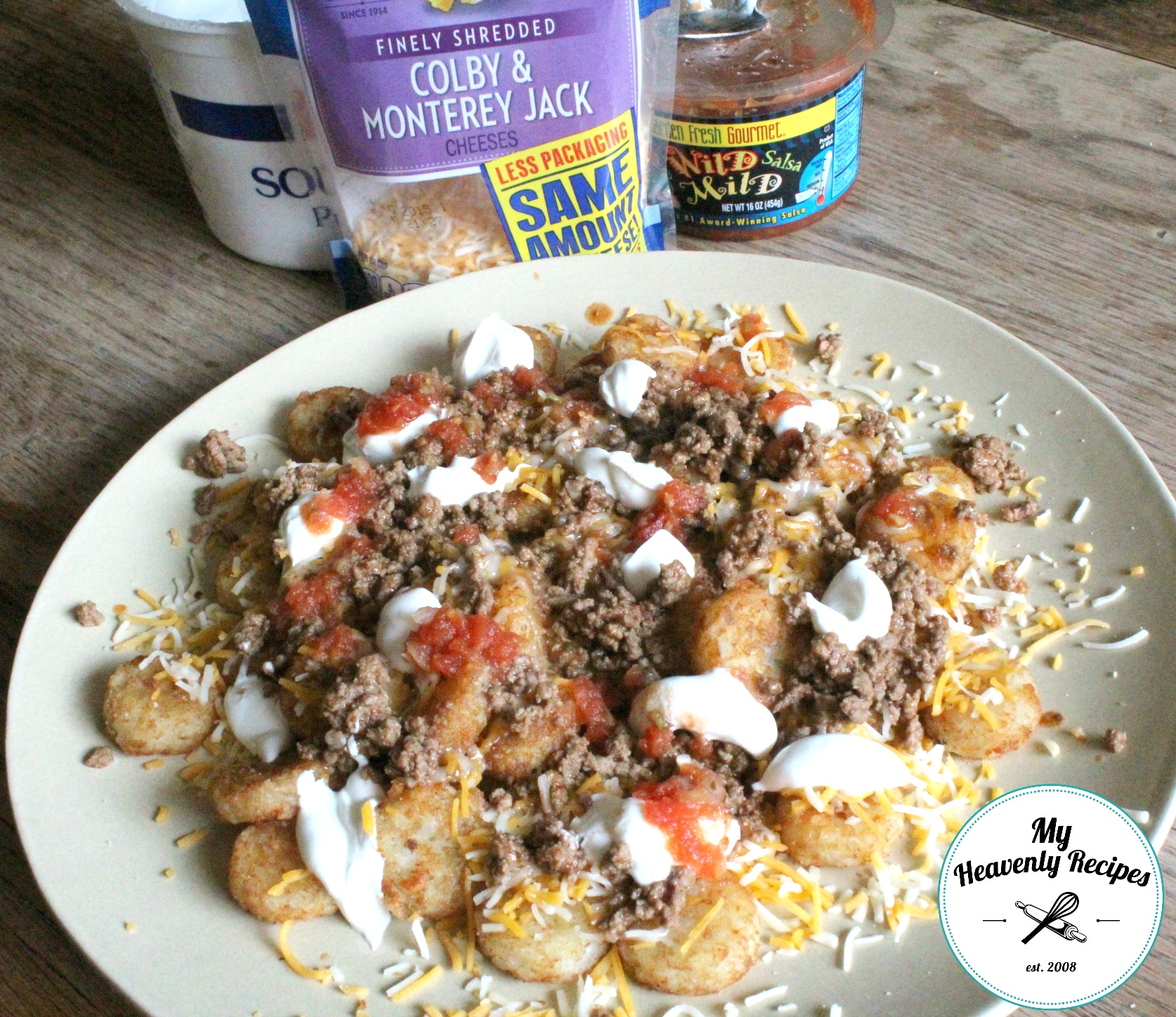 Tater Tot Nachos topped with meat, cheese, tomatoes, and sour cream