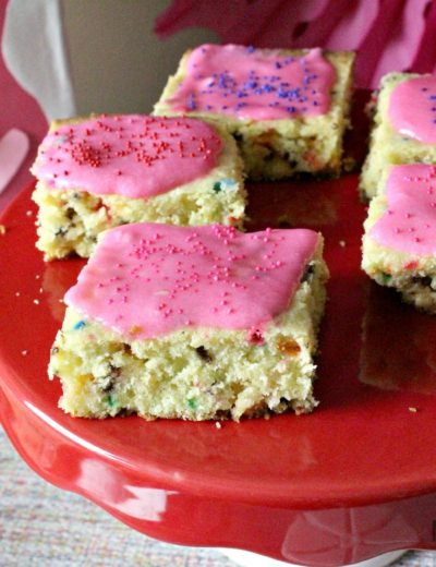 unicorn dessert cookie bars topped with pink frosting and colored sprinkles
