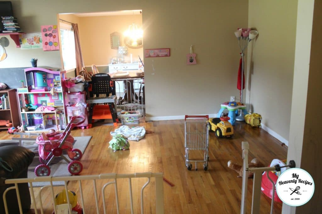 a messy playroom with a barbie house, baby strollers and toys