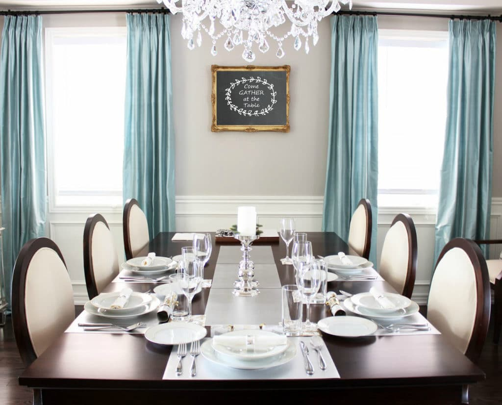 photo of a dining room with art on the wall that says Gather at the table