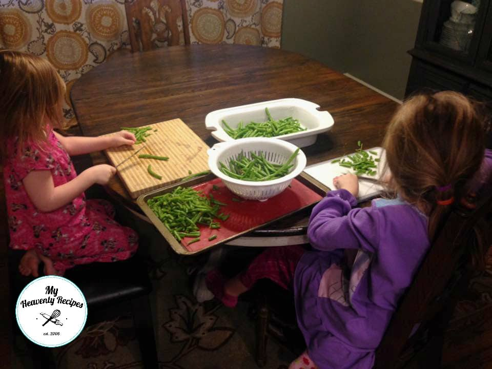 2 little girls sitting at a table trimming green beans on cutting boards