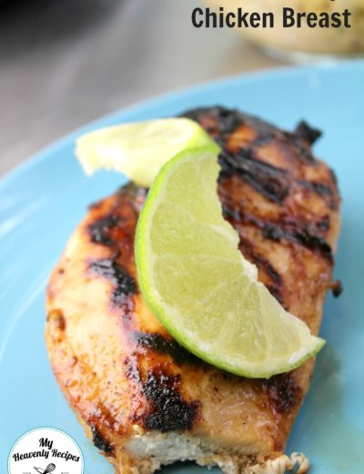 grilled chicken breast with a lemon peel on top served on a blue plate