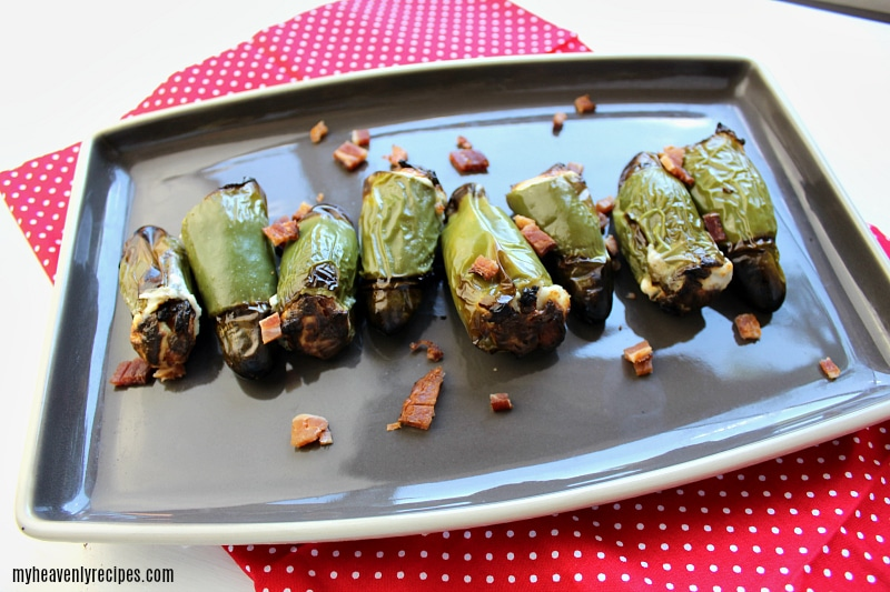 bacon and cream cheese stuffed jalapeno peppers on a serving platter