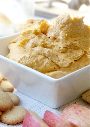 pumpkin dip recipe served in white bowl with apples and vanilla wafers