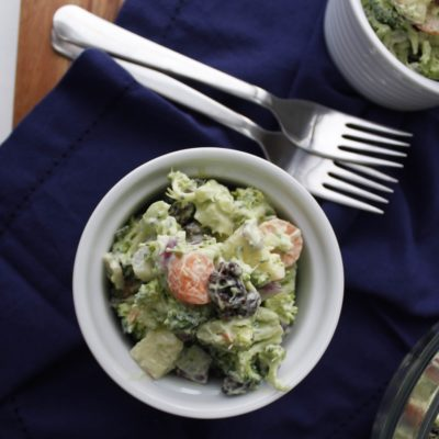 Broccoli Avocado Salad in white bowl with forks on table and blue napkin