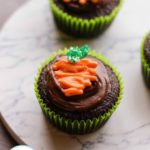 two Easter chocolate cupcakes with chocolate icing topped with candy carrots