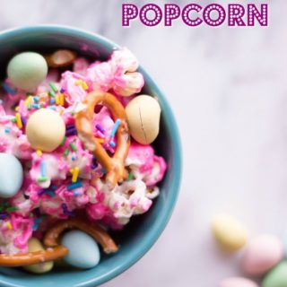 overhead shot of easter popcorn in a pretty blue bowl topped with pretzels and candies