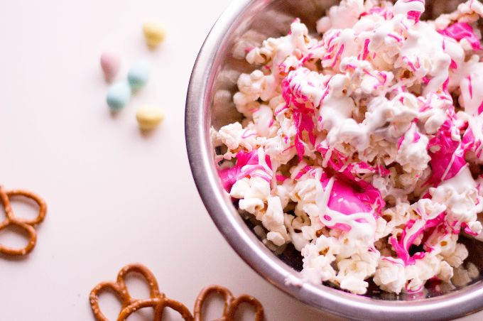 bowl of easter popcorn covered in bright pink and white chocolate next to pretzels and pastel candies