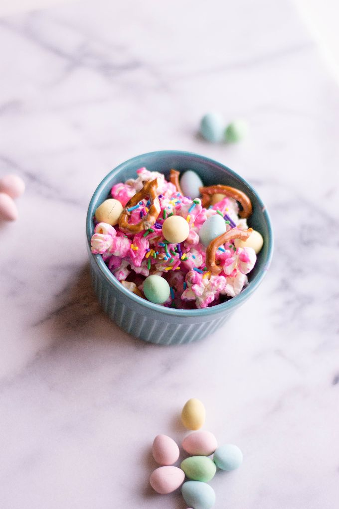 sweet popcorn in a small blue pastel bowl on a countertop surrounded by pastel Easter candies