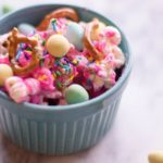 closeup of blue pastel bowl containing waster popcorn with pretzels and pastel candies on top