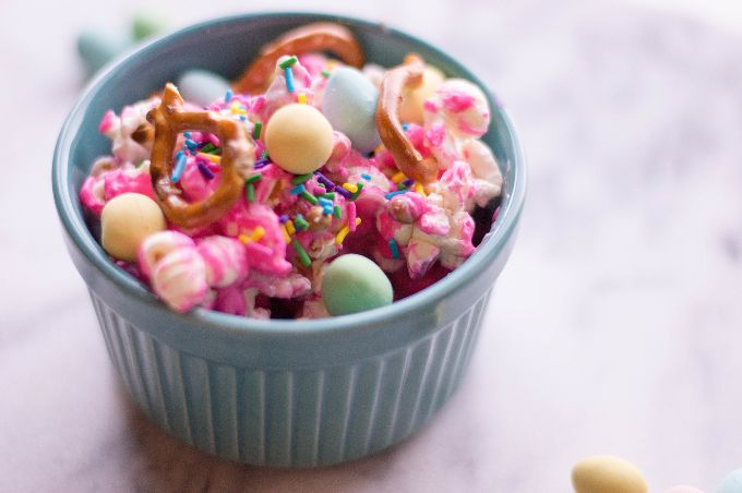 closeup of blue pastel bowl containing sweet popcorn mix with pretzels and pastel candies on top