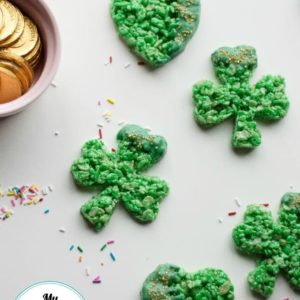 overhead view of several st. patrick's day dessert rice krispies in heart and shamrock shapes next to a bowl of gold tokens