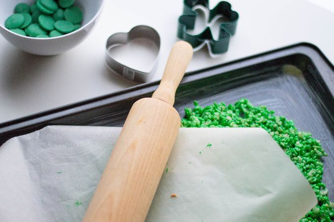 view of rolling pin on top of rice krispies st. patrick's day dessert being rolled out underneath wax paper