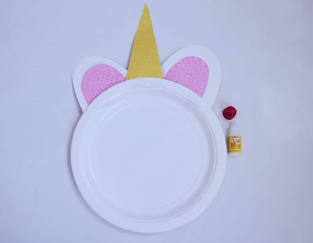 unicorn craft plate without face with horns and ears next to glue