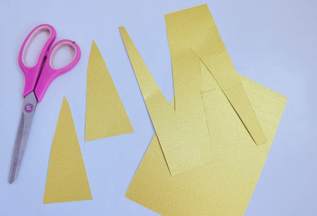 yellow paper cut up next to pink scissors for unicorn craft plate