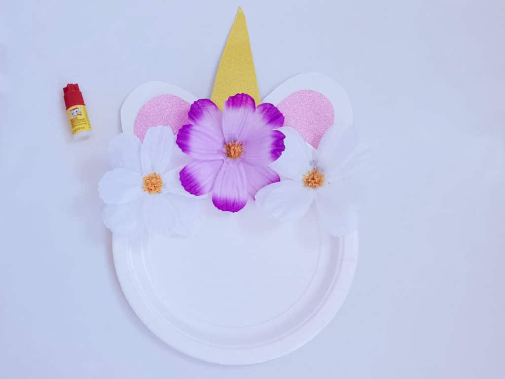 unicorn craft plate almost fully complete with flowers on top next to glue