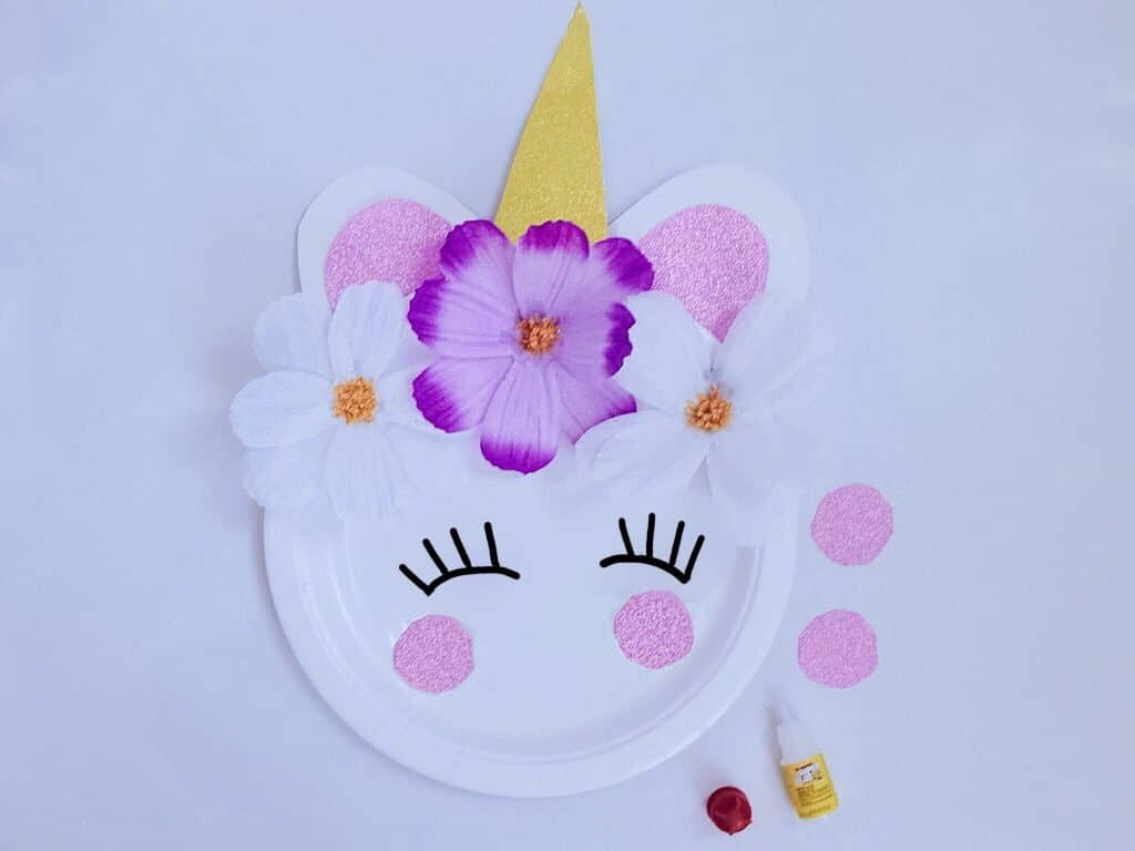 unicorn craft plate with eyelashes drawn on and pink paper dots on top