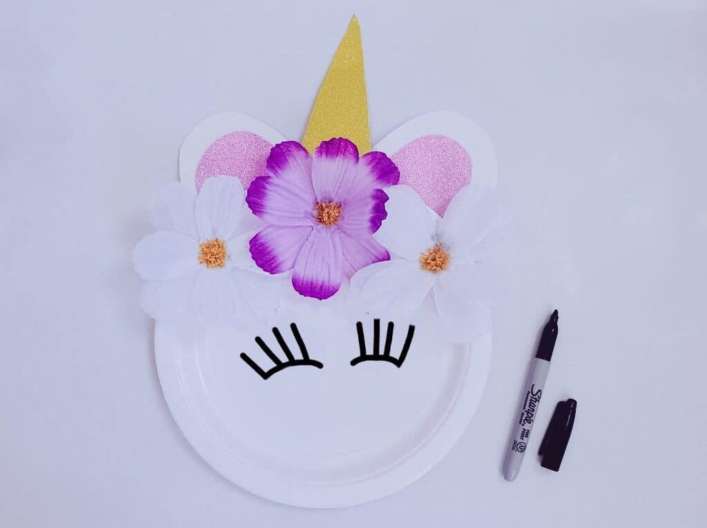 unicorn craft plate with eyelashes drawn on and flowers