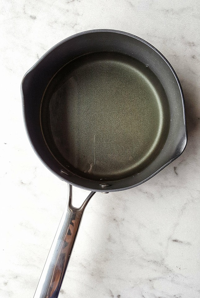 simple syrup being prepared in pan for lemon drop cocktail recipe