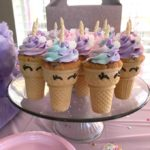 table with pink tablecloth containing a display of unicorn cupcakes on a clear cake tray in front of a window