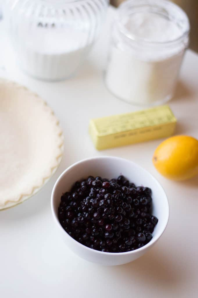 blueberry pie ingredients, blueberries in bowl, lemon, butter, pie shell, sugar in canister in background