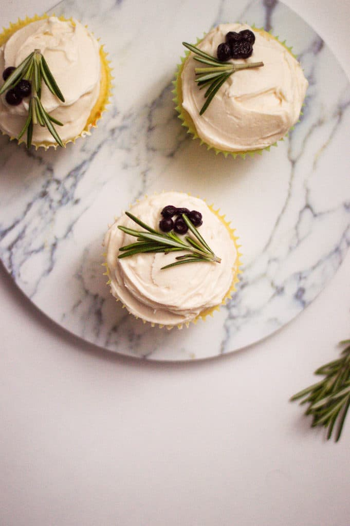 3 moist vanilla cupcakes with vanilla frosting on a marble platter