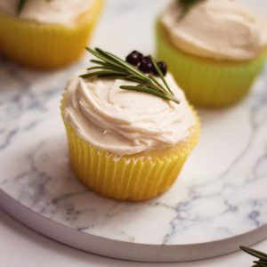 vertical image of 3 vanilla cupcakes with homemade buttercream icing on a marble platter with blueberries and rosemary sprig