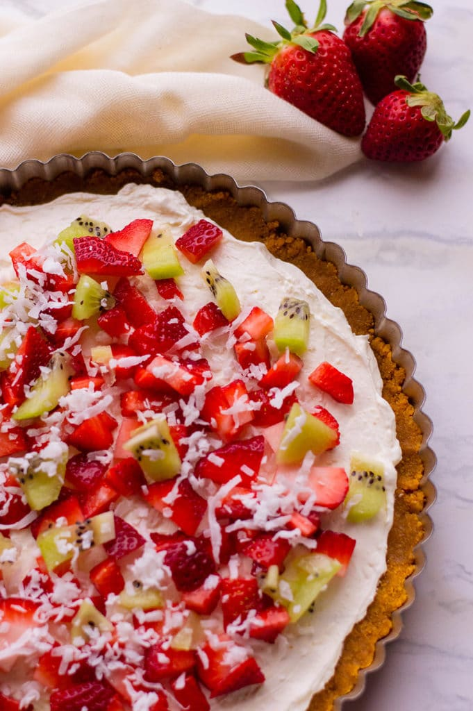 image of dessert pizza recipe with strawberries and kiwi topped with coconut flakes with linen napkin in background horizontal image