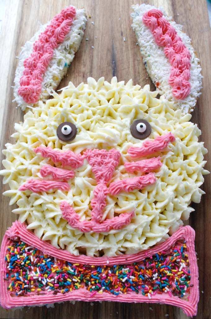 overhead view of easter bunny cake on a brown wooden slab