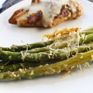 white plate with asparagus topped with parmesan cheese