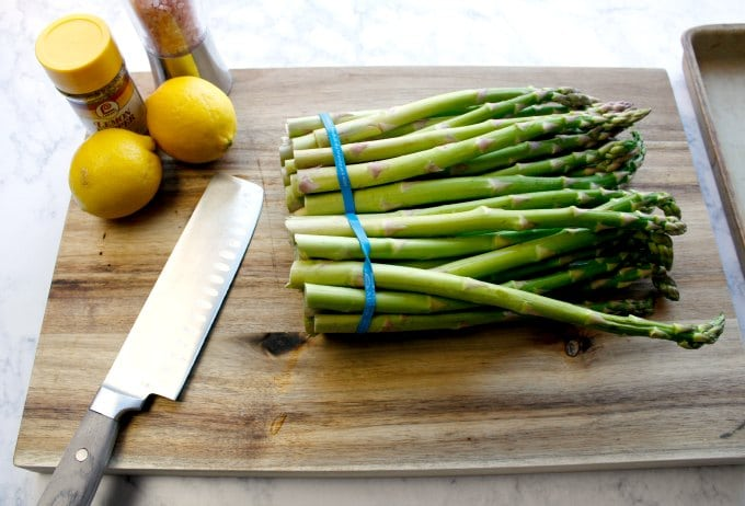 two bunches of asparagus on cutting board next to knife and lemons ready for easy asparagus recipes