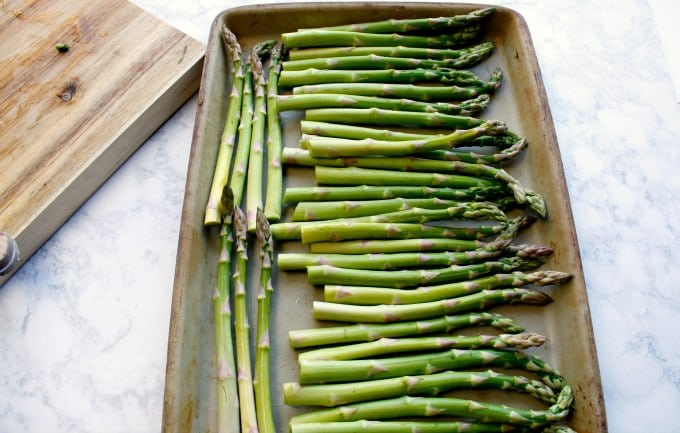 many pieces of asparagus lined on a baking sheet for easy asparagus recipes