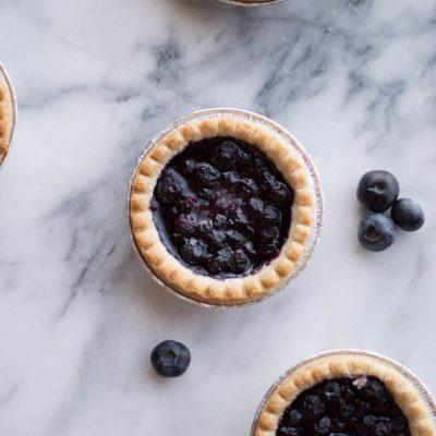 mini blueberry pies on a marble surface
