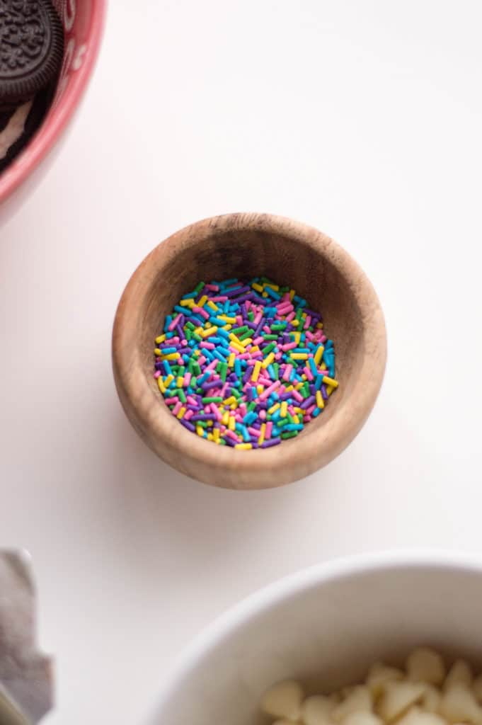 overhead shot of wooden bowl with colored sprinkles