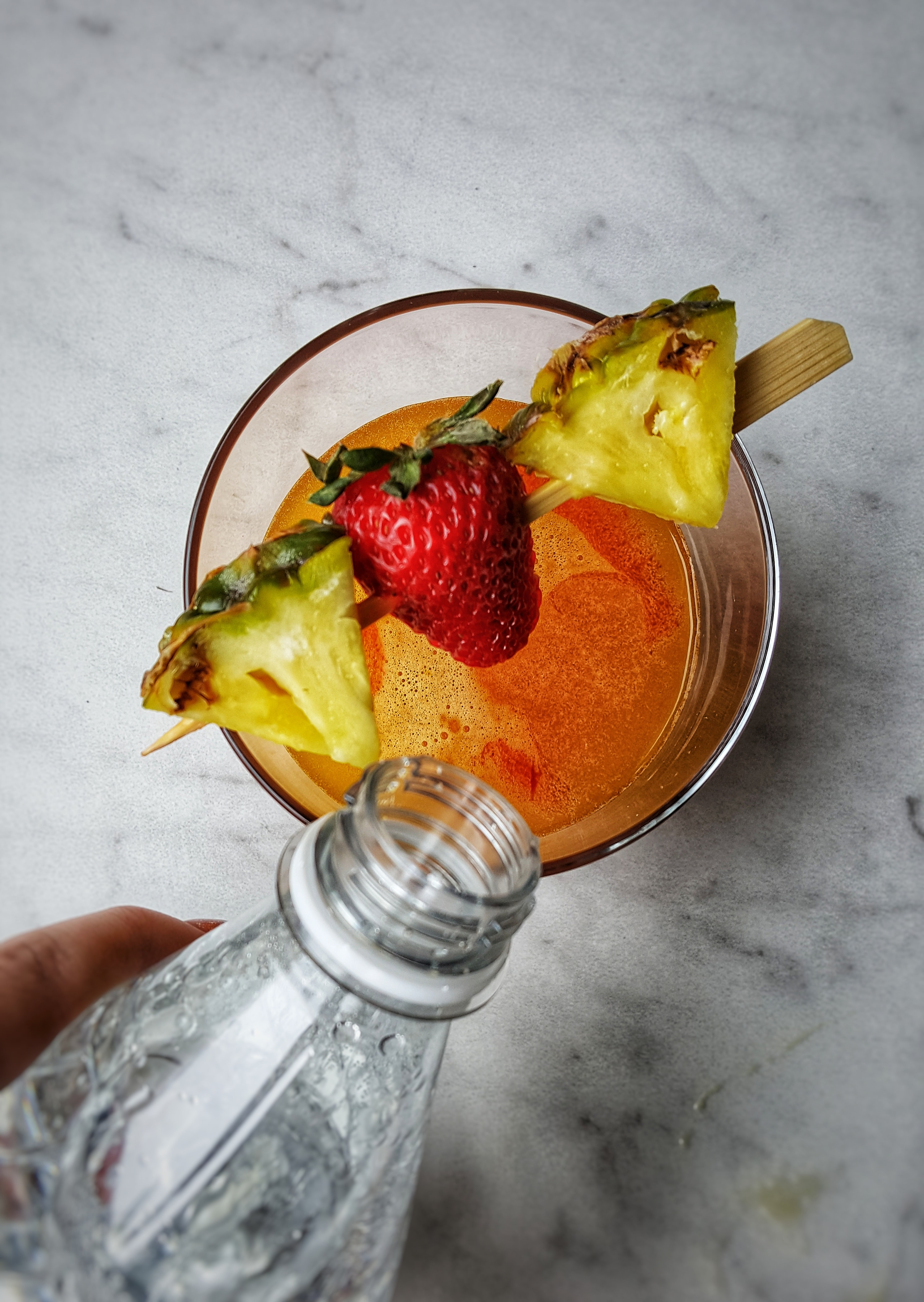 clear glass with pineapple and strawberry on a stick pouring bottle