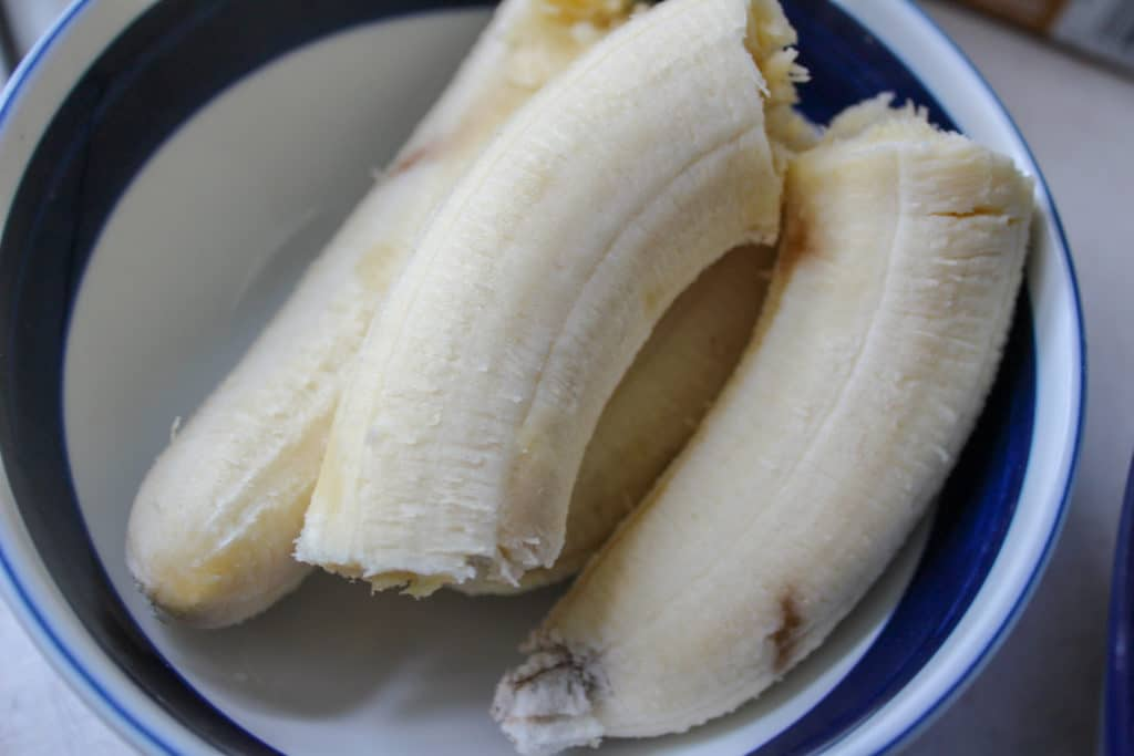 bananas in a bowl with evaporated milk and banana pudding