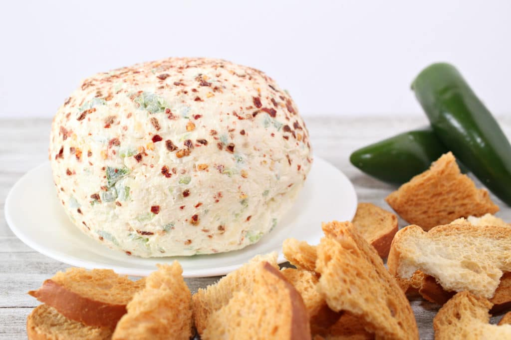 jalapeno cream cheese dip on a white plate with jalapenos in back ground and bread to serve