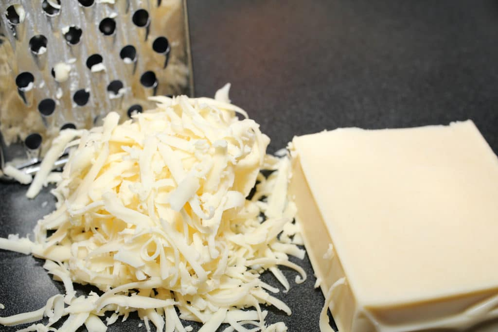 cheese shredded with grater on black surface for jalapeno cream cheese dip