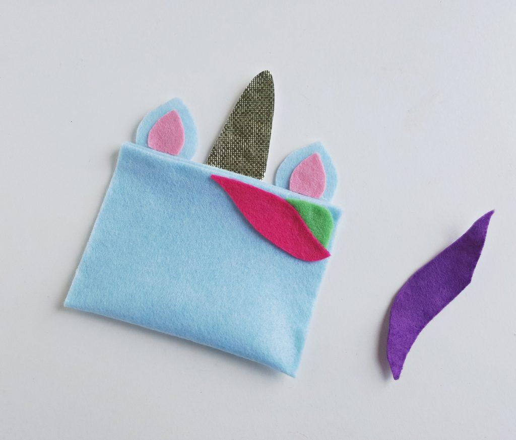 unicorn pencil case pieces next to purple fabric